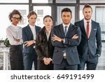 Small photo of young businesspeople in formalwear posing while standing at modern office, multicultural business team