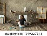 Small photo of Woman painter sitting on the floor in front of an empty canvas and drawing. Art studio interior. Horizontal background. Drawing supplies, oil paints, artist brushes, canvas, frame. Creative concept