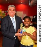 Small photo of NEW YORK CITY - MAY 26 2017: Brooklyn Police Athletic League & King's County DA's office sponsored an afterschool chess program for Bed-Stuy elementary students. Eric Gonzales confers trophies