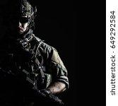 Elite member of US Army rangers in combat helmet and dark glasses. Studio shot, dark black background, looking at camera, dark contrast - stock photo