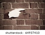 wooden cut-out hand against a wall pointing the direction - stock photo