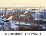 Stock photo elevated skyline of hannover at sunrise in snow with steaming chimneys and train 649490245