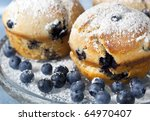 Fresh blueberry muffins, dusted with icing sugar, on crystal plate. - stock photo