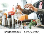 Stock photo bartender preparing different cocktails mixing with straws inside bar profession work and 649726954
