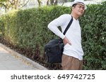 back pain man carrying heavy bag