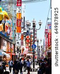 Small photo of OSAKA, JAPAN - 5/26/2017: Shoppers stroll down an alleyway of signs and neon lights in Namba, Osaka, Japan