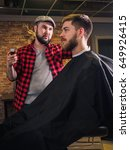 Small photo of Adult male barber and customer in shop. Beard and hairstyle