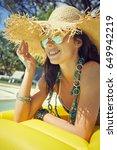 Small photo of woman in bikini sunbathing on air mattress in the swimming pool