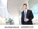 A handsome young business man at office building - stock photo