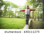 little boy walking on a log in... | Shutterstock . vector #650111275