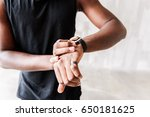 Small photo of Solemn muscular sportsman looking at sport watch