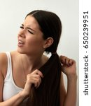 Small photo of The girl tries to untie her hair. Entangled hair. White background.