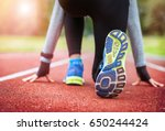 Small photo of Athletic woman on running track getting ready to start run, back view
