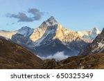 Small photo of Ama Dablam mountain at sunset and blue sky. Sun illuminates slopes. Himalayan mountains, Nepal.