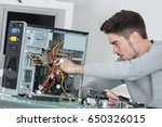 man working on broken computer | Shutterstock . vector #650326015