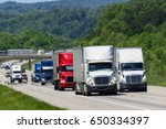 Small photo of A squadron of eighteen-wheelers lead the way down an interstate highway in eastern Tennessee. Heat waves rising from the pavement give a shimmering effect to vehicles and forest in the background.