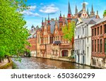 Small photo of Medieval town Bruges in Belgium. Panorama and landscape vintage channel with old brick house broach on roof. Spring sunny day blue sky white cloud end green trees.