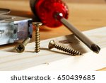Small photo of Screw being screwed into a wooden board, screwdriver and joinery meter with spirit level in background.