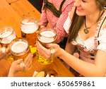 Small photo of Young couple in traditional Bavarian Tracht - Dirndl and Lederhosen - in a beer tent at the Oktoberfest in Munich toasting with their 1 liter beer mugs