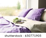 Small photo of Lilac color accent in modern interior. Comfortable bed with book and bouquet in bedroom
