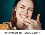 woman eating a burger close up | Shutterstock . vector #650783044