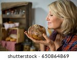 smiling woman smelling a round... | Shutterstock . vector #650864869
