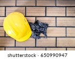 Yellow safety helmet and dirty glove on brown brick floor with copy space and window light