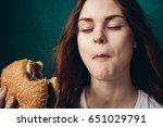 a woman chewing a burger | Shutterstock . vector #651029791