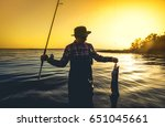 a fisherman with a fishing rod... | Shutterstock . vector #651045661