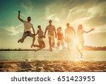 friends jumping on the beach... | Shutterstock . vector #651423955