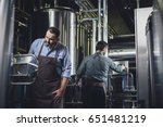 male brewers in aprons working... | Shutterstock . vector #651481219
