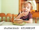 cute little boy eating a stack... | Shutterstock . vector #651488149