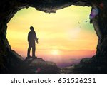 Small photo of Faith God concept: Silhouette humble man standing on cave sunset background.