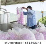 Stock photo rose oil extraction with technology rose oil to extract rose oil man pouring roses in machine 651543145