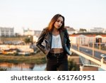 Beautiful young woman in a fashionable leather black jacket and white tank top, jeans vintage jeans urban background