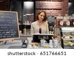 Small photo of small business, people and service concept - happy woman or barmaid at counter with cashbox working in cafe or coffee shop