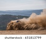 Small photo of Rally car raising the dirt cloud