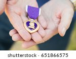 Small photo of Senior Man Holding The Military Purple Heart Medal In His Hands.