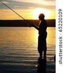 Fisherman in sunset - stock photo