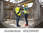 Men In Hardhat And Green Jacke...