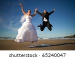 Happiness jump of bride and groom on the beach - stock photo