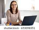 young woman working on a laptop. | Shutterstock . vector #653098351