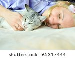 Stock photo woman and her cat are sleeping on the bed 65317444