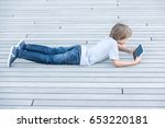 kid with tablet computer lying... | Shutterstock . vector #653220181