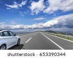 Stock photo white car is driving on the high speed highway on the background of blue cloudy sky 653390344