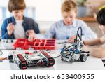 Small photo of Ready made robots at table afore boys