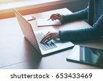 hand with laptop and notebook... | Shutterstock . vector #653433469