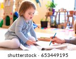 toddler girl drawing picture in ... | Shutterstock . vector #653449195