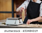 woman scaling noodles in cafe.... | Shutterstock . vector #653484319