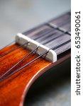 Small photo of Detail of ukulele nut and black nylon strings.